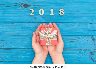 Woman's hands holding gift box near numbers 2018 on blue old table. Flat lay, top view