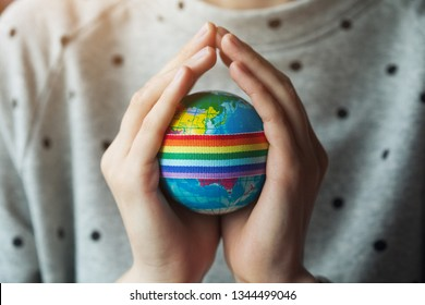 woman's hands holding globe with LGBT rainbow ribbon, gay pride, gender equality problems, bisexual, homosexual people concept