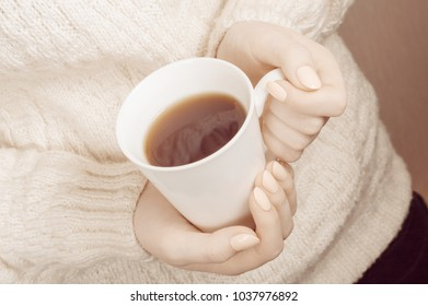 Woman's hands holding hot cup of coffee or tea