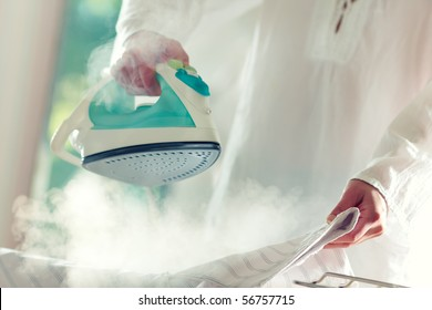 Woman's hands holding hot iron, steaming clothes,shallow depth of field