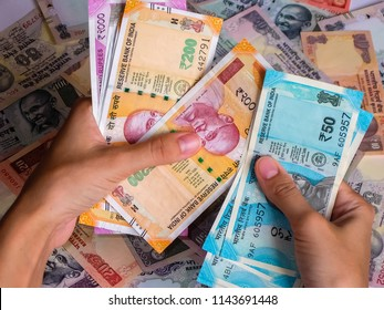 Woman's hands holding indian notes. 10, 20, 50, 100, 200, 500 and 2000 Indian rupees, old and new notes.