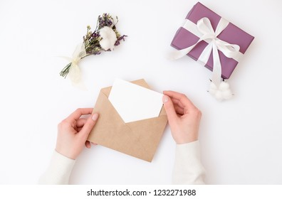 Woman's hands holding kraft envelope with blank wedding invitation card, Gift box, floral minimalist bouquet laying on woman desk. Creative mock up layout on white background, greeting card, top view.