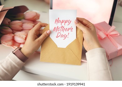 Woman's hands holding a letter in craft envelope. Pink background, Mother's day concept. Tulips flower and pink gift box in background. Womens home desk.