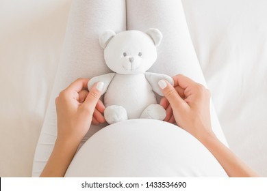 Woman's hands holding little smiling white teddy bear on lap for future baby. Homely atmosphere. Emotional loving moment in pregnancy time - 35 weeks. Baby expectation.