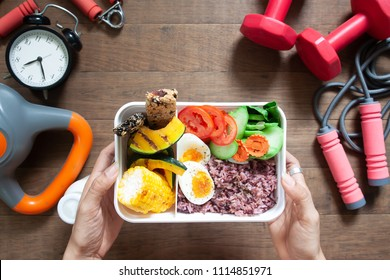Woman's hands holding lunch box with rice berry, boiled eggs, sweetcorn, pumpkin, tomatoes and cereal bars, Top view with sport and fitness equipments on wooden background