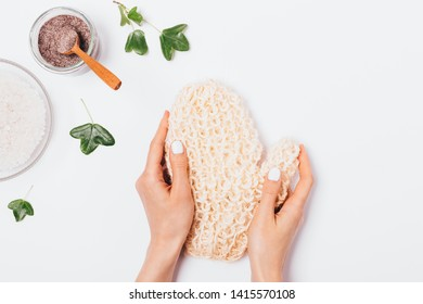 Woman's hands holding natural massage mitten washcloth next to coffee body scrub and bowl of sea salt on white background, top view.