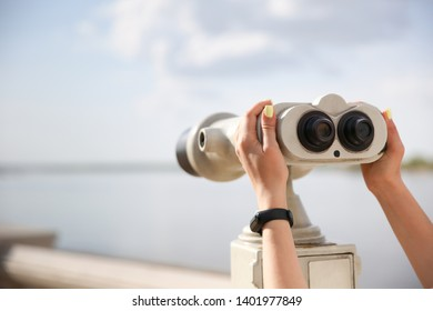 woman's hands holding observation binocular against skyline close up with copy space