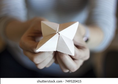 Woman's hands holding a paper fortune teller with blurred background.