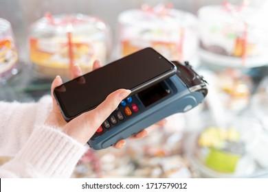 A woman's hands is holding a payment terminal and paying for a purchase using a smartphone. Copy space. The concept of NFC, business and banking transactions