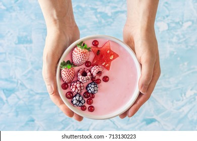 Woman's Hands Holding a Pink Fruit Smoothie Bowl Topped with Frozen Berries and a Watermelon Star