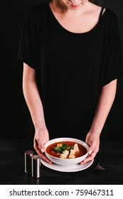 Woman's hands holding a plate of fresh, healthy, spicy, cold, tomato homemade gazpacho soup with basil bread and onion served on black kitchen table. Spanish cuisine. Salt and pepper