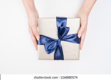 Woman's hands are holding present box with dark blue bow on a isolated background. Festive concept.