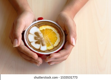 Woman's hands holding a red cup of hot latte coffee topping with beautiful foam milk and orange slices on wooden table.