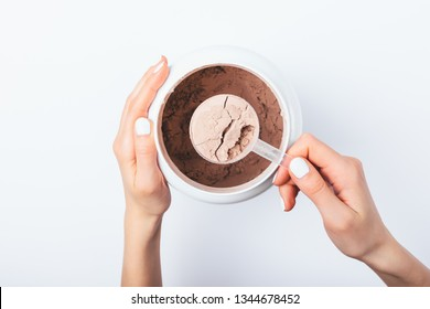Woman's hands holding scoop of chocolate protein powder over jar on white table, view from above.