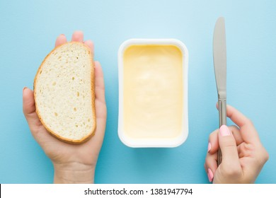Woman's hands holding slice of white bread and knife. Opened plastic pack of light yellow margarine on pastel blue desk. Preparing breakfast. Point of view shot. Closeup.