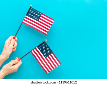 Woman's hands holding small american flags on blue background. Space for text.