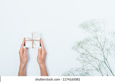 Woman's hands holding small gift box tied with rope near gypsophila flowers on white background, top view. Flat lay minimal composition of giving a present to somebody.