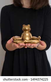 Woman's hands holding smiling gold yoga frog meditating in lotus pose. Body, mind and soul balance concept.