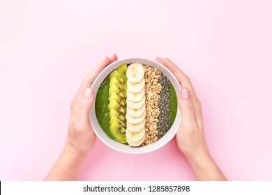 Woman's hands holding spinach smoothie bowl with granola, quinoa, bananas and kiwi on pink background. Top view minimal styled.