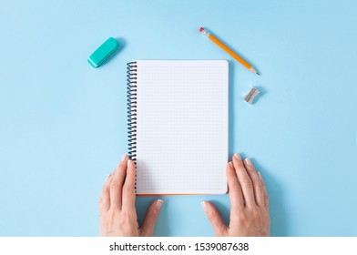 Woman's hands holding a spiral notepad as mockup for your design. Blue pastel background and few office supplies