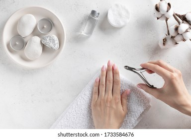 woman's hands holding steel tweezers and cut the cuticle. manicure process. white concrete background, top view. place for text