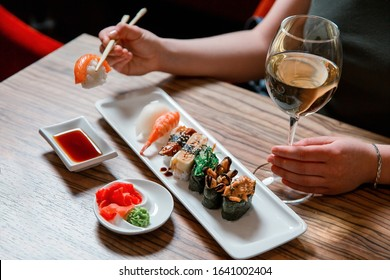 Woman's hands holding sushi with chopsticks and drink white wine, sitting on the wooden table with soy sauce, ginger and wasabi.