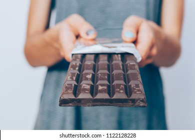 Woman's hands holding unwrapped dark chocolate bar, close-up. Unrecognizable female standing and giving dessert.