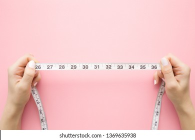 Woman's hands holding white measure tape on pastel pink background. Mock up for body slimming, weight loss or dressmaker's offer or other ideas. Empty place for text, logo or object.