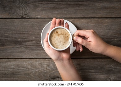 Woman's hands holding worm coffee cup. View from top on a hot cup of coffee.