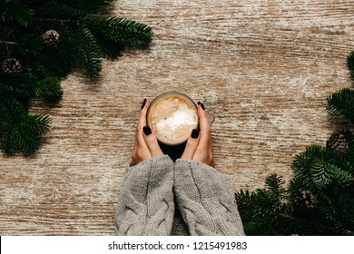 Woman's hands holds a cup of coffee beside spruce branches decoration. Christmas concept. Top view