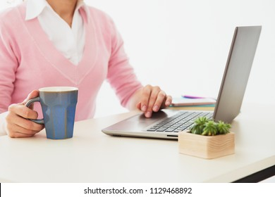 Woman's hands with keyboard of laptop. Office worker typing text on the computer and drinking coffee. Office worker routine