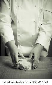 Woman's hands knead dough. Selective focus. Toned.