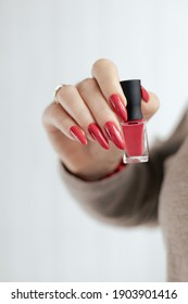 Woman's hands with long nails and a bottle of red orange nail polish