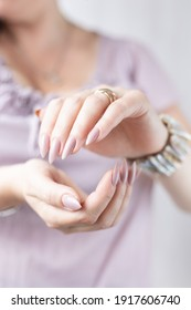 Woman's hands with long nails and light pink bottle manicure with nail polish