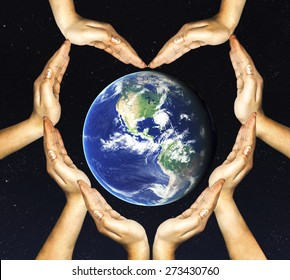 woman's hands make heart shape and earth inside. Elements of this image furnished by NASA