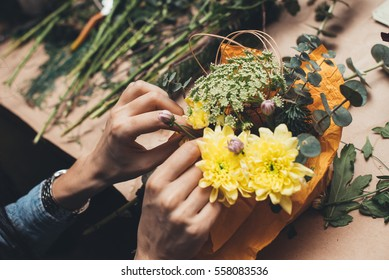 Woman's hands making flower composition at floristic workshop, DIY tools, branches. stems and twine for creative work
