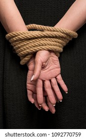 Womans hands on back tied with a rope, long nails