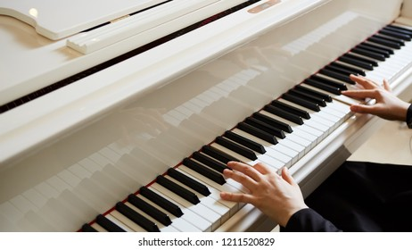 Womans hands on the keyboard of the piano closeup