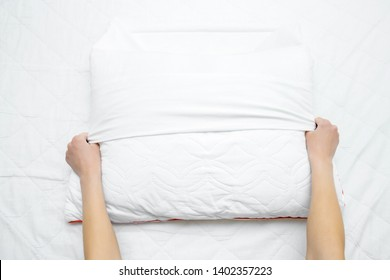 Woman's hands on mattress surface changing white cotton cover on pillow. Regular bed linen change. Closeup. Point of view shot.