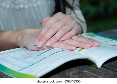 Woman's hands on open book