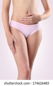 Woman's hands on stomach with pink panties on pink background