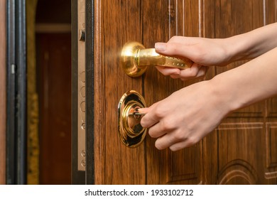 Woman's hands open a brown front door with a gold handle with a key close up