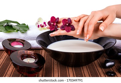 Woman's hands with orchids and bowl of milk