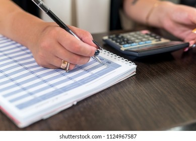 Woman's hands with pen and planner on reception table