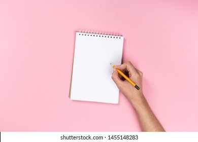 Woman's hands with perfect manicure holding pencil and  notepad as mockup for your design. Pink background, flat lay