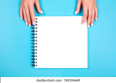 Woman's hands with perfect manicure holding big spiral notepad as mockup for your design. Blue pastel trendy background.