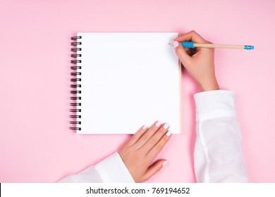 Woman's hands with perfect manicure holding pencil and spiral notepad as mockup for your design. Pink background, flat lay style.