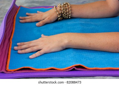 Woman's hands are placed on yoga mat in sphinx position on blue mat with orange trim wearing mala beads.