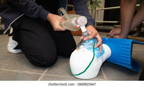 woman's hands practicing cpr on plastic mannequin