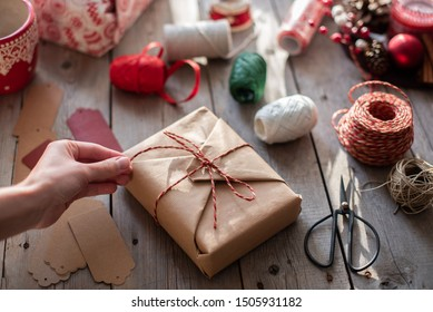 Woman's hands preparing christmas gift decorated